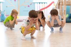 Group of kids squatting on floor in daycare, having fun and playing hide and seek game, hiding the face with hands. Group of children squatting on floor in stock photo