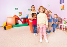 Group of kids stand in kindergarten with teacher. With focus on little girl Royalty Free Stock Photo