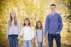 Group of kids standing together and holding hands outdoors. Portrait photo of Four cute kids holding hands together outdoors during an autumn day. Sibling group royalty free stock images