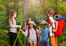 Group of kids talking during hike stop in forest Royalty Free Stock Images