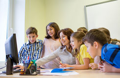 Group of kids with teacher and computer at school. Education, elementary school, learning, technology and people concept - group of school kids with teacher Royalty Free Stock Images