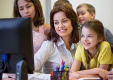 Group of kids with teacher and computer at school. Education, elementary school, learning, technology and people concept - group of school kids with teacher Royalty Free Stock Photos