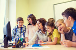 Group of kids with teacher and computer at school. Education, elementary school, learning, technology and people concept - group of school kids with teacher Stock Photography