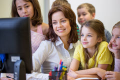 Group of kids with teacher and computer at school. Education, elementary school, learning, technology and people concept - group of school kids with teacher Stock Image