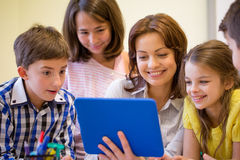 Group of kids with teacher and tablet pc at school Stock Photo
