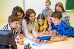 Group of kids with teacher and tablet pc at school Stock Image