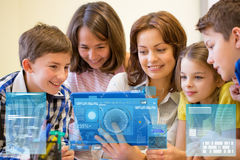 Group of kids with teacher and tablet pc at school Stock Photos