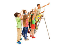 Group of kids trying to be first on ladder Stock Image