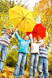 Group of kids with umbrellas. Group of excited kids with red and yellow umbrellas Royalty Free Stock Photo