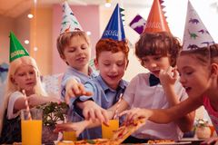 Group of kids visiting birthday party of their classmate. Want to eat. Delighted children expressing positivity while having dinner stock image