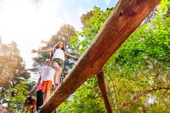 Group of kids walk over high log in the forest Royalty Free Stock Photo