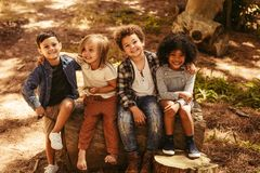 Group of kids on a wooden log. Group of four kids sitting on a wooden log outdoors. Multi-ethnic group of kids playing together in a forest stock photography
