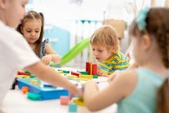 Group of kindergarten kids at day care. Happy children playing with plastic building blocks at kindergarten. Group of kindergarten kids at daycare. Happy stock photos