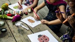 Group of kindergarten kids friends drawing art class outdoors stock photos