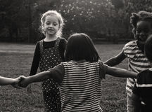 Group of kindergarten kids friends holding hands playing at park Stock Photo