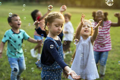 Group of kindergarten kids friends playing blowing bubbles fun royalty free stock photos