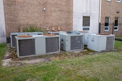 Group of large air conditioner compressors outside commerical building. Group of mulitple air conditioner units outside commerical building royalty free stock photography