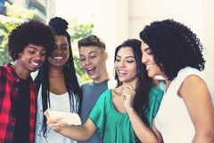 Group of latin american and african young adults watching clip. Outdoor in the city stock images