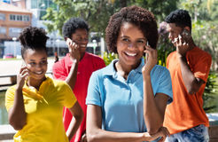 Group of latin american young adult talking at phone. Outdoor in the summer in the city Royalty Free Stock Photos