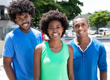Group of laughing african american young adults. In the city with buildings and green plants and trees in the background Royalty Free Stock Image