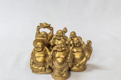 Group of Laughing Buddha painted in gold colour in a white backdrop. Macro with extremely shallow depth of field Stock Photo