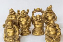 Group of Laughing Buddha painted in gold colour in a white backdrop. Macro with extremely shallow depth of field Stock Images