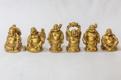Group of Laughing Buddha painted in gold colour in a white backdrop. Macro with extremely shallow depth of field Royalty Free Stock Image