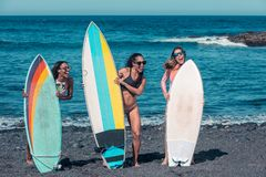 Playful women with surfboards on beach stock photography