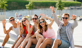 Group of laughing friends sitting on city square Stock Photos