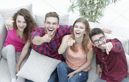 Group of laughing friends sitting on sofa and showing forefinger on the camera. View from the top.a group of laughing friends sitting on sofa and showing stock image