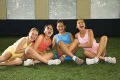 Group laughing girls. Four multiethnic girls sitting with arms around eachother laughing Royalty Free Stock Photo