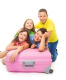 Group of laughing kids isolated on white. Group of four happy kids laying funny and laughing on suit case, isolated on white Royalty Free Stock Photography