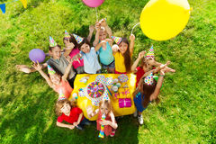 Group of laughing kids standing around B-day cake Royalty Free Stock Photo