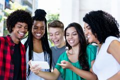 Group of laughing latin american and african young adults watching clip. Outdoor in the city stock image