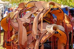 Group Of Leather Saddles At A Market Stall. A group of leather saddles for sale at a country market stall stock photo