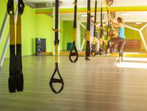 Group lesson with a trainer and training on the TRX sport loop in the new modern fitness complex, copy space, people. Group lesson with a trainer and training on royalty free stock photos