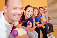 Group lifting dumbbells in fitness. Happy group lifting dumbbells in a fitness center gym Royalty Free Stock Photo