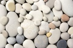 Group of light small and big pebbles. In two layers, simple stones background Stock Photo