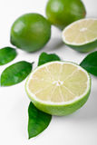 Group of limes. Close up of a group of three limes with leaves one cut in half Stock Images