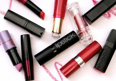 Group of lipsticks on white background. A consistent group of lipsticks in different colors and shapes (with zig-zag shades of lipstick on ground), photographed stock photos