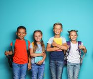 Group of little children with backpacks. And school supplies on color background stock image