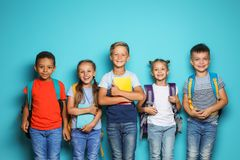 Group of little children with backpacks school supplies on color background