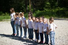 Group of little children different ages lined up in line in summer park. Close up stock image