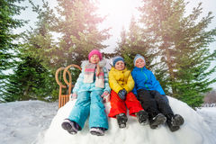Group of little children sit on snow wall in park Stock Photos
