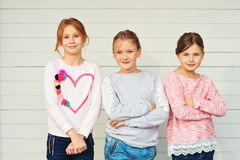 Little girls portrait. Group of 3 little girls standing outdoors against white wooden background, wearing denim jeans and sweatshirts stock image