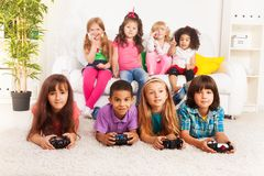 Group of little kids playing video game. Close portrait of a group of diversity looking kids, boys and girls playing videogame laying on the floor in kids room Royalty Free Stock Image