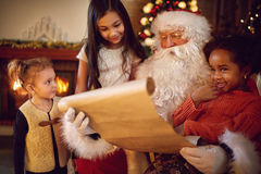 Group of little multi ethnic girls looking in Santa Claus with w Royalty Free Stock Photography