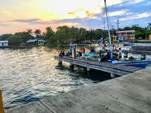 A group of local Belizean fisherman return their boat to the dock after a day of fishing as the sun sets royalty free stock photo