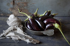 Group of long eggplants on vintage plate on wooden table Stock Photography