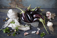 Group of long eggplants on vintage plate on wooden table with garlic and parsley Royalty Free Stock Photography